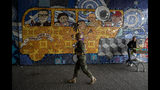 Chilean Army soldier walks in front a mural representing late chilean President Salvador Allende while guarding a subway station during a second day protests in Santiago, Chile, Saturday, Oct. 19, 2019. The protests started on Friday afternoon when high school students flooded subway stations, jumping turnstiles, dodging fares and vandalizing stations as part of protests against a fare hike, but by nightfall had extended throughout Santiago with students setting up barricades and fires at the entrances to subway stations, forcing President Sebastian Pinera to announce a state of emergency and deploy the armed forces into the streets. (AP Photo/Esteban Felix)
