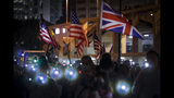 Protesters fresh their smartphone's lights near the British and American flags to give support the prayer rally at Edinburgh Place in Hong Kong, Saturday, Oct. 19, 2019. Hong Kong pro-democracy protesters are set for another weekend of civil disobedience as they prepare to hold an unauthorized protest march to press their demands. (AP Photo/Mark Schiefelbein)