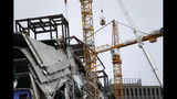Workers in a bucket hoisted by a crane begin the process of preparing the two unstable cranes for implosion at the collapse site of the Hard Rock Hotel, which underwent a partial, major collapse while under construction last Sat., Oct., 12, in New Orleans, Friday, Oct. 18, 2019. Plans have been pushed back a day to bring down two giant, unstable construction cranes in a series of controlled explosions before they can topple onto historic New Orleans buildings, the city's fire chief said Friday, noting the risky work involved in placing explosive on the towers. (AP Photo/Gerald Herbert)