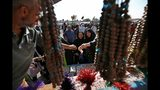 Iranian Shiite pilgrims shop for religious items outside the holy shrine of Imam Hussein ahead of the Arbaeen festival in Karbala, Iraq, Friday, Oct. 18, 2019. The holiday marks the end of the forty day mourning period after the anniversary of the martyrdom of Imam Hussein, the Prophet Muhammad's grandson in the 7th century. (AP Photo/Hadi Mizban)