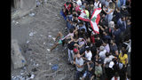 Anti-government protesters try to remove a barbed-wire barrier to advance towards the government buildings during a protest in Beirut, Lebanon, Saturday, Oct. 19, 2019. The blaze of protests was unleashed a day earlier when the government announced a slate of new proposed taxes, including a $6 monthly fee for using Whatsapp voice calls. The measures set a spark to long-smoldering anger against top leaders from the president and prime minister to the numerous factional figures many blame for decades of corruption and mismanagement. (AP Photo/Hassan Ammar)