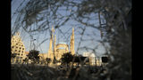 Mohammad Al-Amin Mosque is seen through a broken glass door of a shop after a protest against the Lebanese government in Beirut, Lebanon, Saturday, Oct. 19, 2019. The blaze of protests was unleashed a day earlier when the government announced a slate of new proposed taxes, including a $6 monthly fee for using Whatsapp voice calls. The measures set a spark to long-smoldering anger against top leaders from the president and prime minister to the numerous factional figures many blame for decades of corruption and mismanagement. (AP Photo/Hassan Ammar)