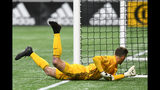 New England Revolution goalkeeper Matt Turner tries to stop a kick on goal by Atlanta United defender Franco Escobar who scored during the second half of round one of an MLS Cup playoff soccer game Saturday, Oct. 19, 2019, in Atlanta. Atlanta United won 1-0. (AP Photo/John Amis)