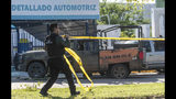 """A Mexican police officer deploys tape to secure the scene around a bullet riddled armed forces truck, a day after gunmen and members of Mexico security forces clashed in a large gun battle in Culiacan, Mexico, Friday Oct. 18, 2019. Mexican security forces backed off an attempt to capture a son of imprisoned drug lord Joaquin """"El Chapo"""" Guzman after finding themselves outgunned in a ferocious shootout with cartel enforcers that left at least eight people dead and more than 20 wounded, authorities said Friday. (AP Photo/Augusto Zurita)"""