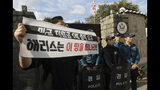 "In this Friday, Oct. 18, 2019, photo, a college student holds a banner in front of the U.S. ambassador's residence in Seoul, South Korea. South Korean police said Saturday, Oct. 19, they beefed up security at the U.S. ambassador's residence in Seoul after a group of anti-American students used ladders to break into the compound. The sign reads "" ""Harris, leave this land!"" (Chun Jin-hwan/Newsis via AP)"