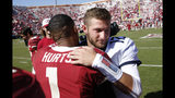 West Virginia quarterback Austin Kendall (12) and Oklahoma quarterback Jalen Hurts (1) embrace following an NCAA college football game in Norman, Okla., Saturday, Oct. 19, 2019. Oklahoma won 52-14. (AP Photo/Alonzo Adams)