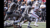 Wisconsin running back Jonathan Taylor (23) runs the ball as Illinois' Oluwole Betiku, Jr (47) and Stanley Green (7) chase during the first half of an NCAA college football game, Saturday, Oct.19, 2019, in Champaign, Ill. (AP Photo/Holly Hart)
