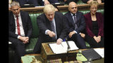 Britain's Prime Minister Boris Johnson speaks to lawmakers inside the House of Commons to update details of his new Brexit deal with EU, in London Saturday Oct. 19, 2019. At a rare weekend sitting of Parliament, Johnson implored legislators to ratify the Brexit deal he struck this week with the other 27 EU leaders. Secretary of State for Exiting the European Union, Stephen Barclay, left, and Business Secretary Andrea Leadsom, right. (Jessica Taylor/House of Commons via AP)