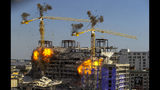 Two large cranes from the Hard Rock Hotel construction collapse come crashing down after being detonated for implosion in New Orleans, Sunday, Oct. 20, 2019. Officials set off thundering explosions Sunday to topple two cranes looming precariously over a partially collapsed hotel in New Orleans, but most of one crane appeared to be left dangling atop the ruined building while the other crashed down. (David Grunfeld/The Advocate via AP)