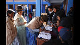 A woman signs on a voters record after voting at a polling station during general elections in La Paz outskirts, Bolivia, Sunday, Oct. 20, 2019. Bolivians are voting in general elections Sunday where President Evo Morales is Presidential candidate for a fourth term. (AP Photo/Jorge Saenz)