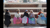 Women sit outside a polling station during general elections in La Paz outskirts, Bolivia, Sunday, Oct. 20, 2019. Bolivians are voting in general elections Sunday where President Evo Morales is Presidential candidate for a fourth term. (AP Photo/Jorge Saenz)