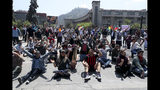 Demonstrators sit in Santiago, Chile, Sunday, Oct. 20, 2019. Protests in the country have spilled over into a new day, even after President Sebastian Pinera cancelled the subway fare hike that prompted massive and violent demonstrations. (AP Photo/Esteban Felix)