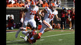 Clemson quarterback Trevor Lawrence (16) escapes from the grasp of Louisville linebacker Monty Montgomery (7) during the second half of an NCAA college football game in Louisville, Ky., Saturday, Oct. 19, 2019. Clemson won 45-10. (AP Photo/Timothy D. Easley)