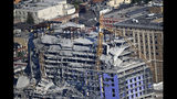 Two large cranes from the Hard Rock Hotel construction collapse are seen in this aerial photo after crashing down, after being detonated for implosion in New Orleans, Sunday, Oct. 20, 2019. (AP Photo/Gerald Herbert)