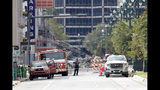 Fire department pesonnel stand by as workers prepare two unstable cranes for implosion at the collapse site of the Hard Rock Hotel, which underwent a partial, major collapse while under construction last Sat., Oct., 12, in New Orleans, Saturday, Oct. 19, 2019. Authorities plan to blow up the two towering construction cranes that have become unstable at the site of the collapsed hotel. They hope to bring down the cranes with series of small controlled blasts just ahead of approaching tropical weather. The mayor has imposed a state of emergency to seize property and force people out if necessary. They hope to avoid more damage to gas and power lines and historic buildings. (AP Photo/Gerald Herbert)