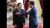 Indonesian President Joko Widodo, right, shows the way to Cambodia's Prime Minister Hun Sen during their meeting ahead of Widodo's inauguration, at Merdeka Palace in Jakarta, Indonesia, Sunday, Oct. 20, 2019. (AP Photo/Dita Alangkara)