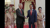 Indonesian President Joko Widodo, second from right, shakes hands with Singapore's Prime Minister Lee Hsien Loong as Lee's wife Ho China, left, and Widodo's wife Iriana Joko Widodo look on during their meeting ahead of Widodo's inauguration, at Merdeka Palace in Jakarta, Indonesia, Sunday, Oct. 20, 2019. (AP Photo/Dita Alangkara)