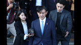 South Korean Justice Minister Cho Kuk, center, leaves the Gwacheon Government Complex in Gwacheon, South Korea, Monday, Oct. 14, 2019. Cho on Monday offered to step down amid an investigation into allegations of financial crimes and academic favors surrounding his family, a scandal that has rocked Seoul's liberal government and deeply polarized national opinion. (Ryu Hyung-suck/Yonhap via AP)