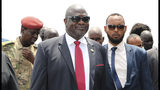 South Sudan opposition leader Riek Machar, centre, as he returns to the country, in Juba, Saturday, Oct. 19, 2019, to meet with President Salva Kiir less than a month before their deadline to form a unity government after a five-year civil war. Machar's two-day visit includes a scheduled meeting with the U.S. ambassador to the United Nations, who arrives Sunday with a U.N. Security Council delegation.(AP Photo/Sam Mednick)