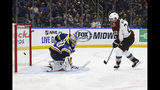 Colorado Avalanche's Colin Wilson (22) watches as St. Louis Blues goaltender Jordan Binnington (50) deflects the puck during the second period of an NHL hockey game Monday, Oct. 21, 2019, in St. Louis. (AP Photo/Scott Kane)