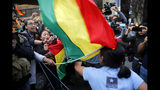 Supporters of opposition presidential candidate Carlos Mesa, a former president, top, use their flag to hit a supporter of Bolivian President Evo Morales, who is running for reelection, his fourth term, as rival groups gather outside the Supreme Electoral Court where election ballots are being counted in La Paz, Bolivia, Monday, Oct. 21, 2019. A sudden halt in release of presidential election returns led to confusion and protests in Bolivia on Monday as opponents suggested officials were trying to help Morales avoid a risky runoff. (AP Photo/Jorge Saenz)