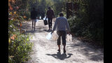 Migrants carry empty canisters to be filled with a water near the Vucijak refugee camp outside Bihac, northwestern Bosnia, Monday, Oct. 21, 2019. Authorities in the town of Bihac on Monday stopped the delivery of water supplies to the Vucjak camp saying they want to draw attention to the problems in the camp set up on a former landfill and near mine fields from the 1992-95 war. (AP Photo/Eldar Emric)