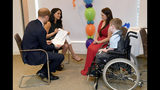 Britain's Prince Harry and Duchess of Sussex, left, look at a t-shirt designed by William Mgee and mother Kelly during the annual WellChild Awards in London, Tuesday Oct. 15, 2019. The WellChild Awards celebrate the inspiring qualities of some of the country's seriously ill young people.(Toby Melville/Pool via AP)