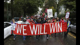 """Dozens of Chicago Teachers Union members and supporters march through the streets of Chicago's Hyde Park neighborhood during the """"Nurse in Every School"""" Solidarity March for Justice on Monday, Oct. 21, 2019. (Antonio Perez/Chicago Tribune via AP)"""