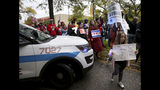 """Dozens of Chicago Teachers Union members, CPS students and supporters march around a police car blocking the street and continue to march through the streets of Chicago's Hyde Park neighborhood during the """"Nurse in Every School"""" Solidarity March for Justice on Monday, Oct. 21, 2019. (Antonio Perez/Chicago Tribune via AP)"""