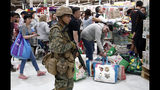 A military police stands guard at a supermarket as customers wait in line, in Santiago, Chile, on Monday, Oct. 21, 2019. Chile's capital seemed to return to calm Monday after three days of protests and acts of vandalism sparked by a rise in subway fares. (AP Photo/Luis Hidalgo)