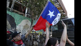 """Protesters wave a Chilean national flag as they stand in front of an armored vehicle, in Santiago, Chile, Monday, Oct. 21, 2019. Hundreds of protesters are defying an emergency decree to confront police in Chile's capital, continuing disturbances that have left at least 11 dead and led the president to say the country is """"at war."""" (AP Photo/Miguel Arenas)"""