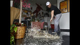 FILE - In this Jan. 5, 2016, file photo, Chris Lene sweeps water out of one of the businesses in the building he owns that was flooded by rainwater in Sacramento, Calif. Climate change is making stronger El Ninos, which change weather worldwide and heat up an already warming planet, according a study in Proceedings of the National Academy of Sciences on Monday, Oct. 21, 2019. (AP Photo/Rich Pedroncelli, File)