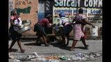 Vendedores recogen sus productos para resguardarse mientras se aproximan manifestantes que exigen la renuncia del presidente Jovenel Moïse en Puerto Príncipe, Haití, el lunes 21 de octubre de 2019. (AP Foto/Rebecca Blackwell)