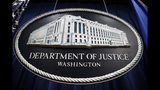 FILE - In this Thursday, April 18, 2019, file photo, a sign for the Department of Justice hangs in the press briefing room at the Justice Department, in Washington. (AP Photo/Patrick Semansky, File)