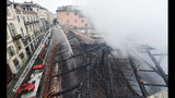 Firefighters put out a fire on the rooftop of the Cavallerizza Reale, in Turin, northern Italy, Monday, Oct. 21, 2019. A big fire broke out on Monday at Turin's Cavallerizza Reale, a historic building in the centre of the northern city which has UNESCO World Heritage status thanks to its special architectural features, no injuries were reported. (Alessandro Di Marco/ANSA via AP)