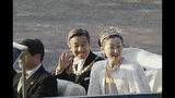 FILE - In this Nov. 12, 1990, file photo, then Japan's Emperor Akihito, center, waves as then Empress Michiko smiles as they start an open car parade from the palace in Tokyo. Japan is abuzz ahead of a ceremony Tuesday, Oct. 22, 2019, marking Emperor Naruhito's ascension to the Chrysanthemum Throne. It is one of several formal ceremonies for Naruhito, 59, who has been a full-fledged emperor since succeeding in May after the abdication of his father, Akihito.(AP Photo/Koji Sasahara, File)