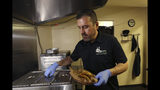 In this Thursday, Oct. 10, 2019 photo, Jose Gamiz, a co-owner at the Mi Vegana Madre restaurant, prepares fresh vegan tacos in Glendale, Ariz. No longer just a few items on a mainstream restaurant's menu, vegan Mexican food has become a widening industry on its own with Latinos taking control of the kitchen. (AP Photo/Ross D. Franklin)