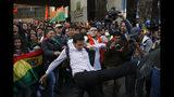 Partidarios del candidato opositor y expresidente Carlos Mesa retienen a un compañero que intenta patear a los simpatizantes del presidente boliviano Evo Morales, que se postuló a un cuarto período, frente al Tribunal Supremo Electoral, en La Paz, Bolivia, el lunes 21 de octubre de 2019. (AP Foto/Jorge Saenz)