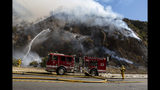 Firefighters begin hosing down the flames of a wildfire called the Palisades Fire minutes after it ignites on Monday, Oct. 21, 2019 in Pacific Palisades, a suburb of Los Angeles. A furious firefighting air and ground attack beat back the wildfire Monday as it raced up canyon walls toward multimillion-dollar ocean-view homes on a ridge in Los Angeles. (AP Photo/Christian Monterrosa)