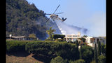 A Los Angeles County Fire Department helicopter makes a water drop as flames from a wildfire threaten homes on a ridgeline in the Pacific Palisades area of Los Angeles Monday, Oct. 21, 2019. (AP Photo/Reed Saxon)