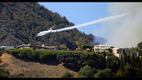 A plane makes a drop in a canyon behind a ridgeline as a wildfire threatens homes in the Pacific Palisades area of Los Angeles Monday, Oct. 21, 2019. (AP Photo/Reed Saxon)