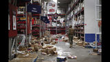 A soldier walks inside a looted supermarket in Santiago, Chile, Tuesday, Oct. 22, 2019. Chile has been facing days of unrest, triggered by a relatively minor increase in subway fares. The protests have shaken a nation noted for economic stability over the past decades, which has seen steadily declining poverty despite persistent high rates of inequality. (AP Photo/Luis Hidalgo)