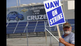FILE - In this Sept. 16, 2019, file photo a picketer carries sign at one of the gates outside the closed General Motors automobile assembly plant in Lordstown, Ohio. Many from Lordstown, Ohio, and near Baltimore and Detroit are opposing a deal that could end a 37-day strike that crippled GM's U.S. production and cost the company an estimated $2 billion. (AP Photo/Keith Srakocic, File)