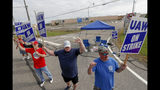 FILE - In this Sept. 16, 2019, file photo picketers carry signs at one of the gates outside the closed General Motors automobile assembly plant in Lordstown, Ohio. Many from Lordstown, Ohio, and near Baltimore and Detroit are opposing a deal that could end a 37-day strike that crippled GM's U.S. production and cost the company an estimated $2 billion. (AP Photo/Keith Srakocic, File)