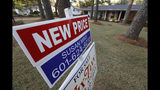 This Sept. 25, 2019, photo shows a sign indicating a new selling price for a house sits atop a realtor's sign in Jackson, Miss. On Tuesday, Oct. 22, the National Association of Realtors reports on sales of existing homes in September. (AP Photo/Rogelio V. Solis)