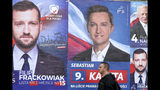 A pedestrian walks past electoral posters in Warsaw, Poland, Monday, Oct. 14, 2019. Nearly complete results in Poland's weekend election confirm that the conservative ruling party Law and Justice capitalized on its popular social spending policies and social conservatism to do better than when it swept to power four years ago. (AP Photo/Czarek Sokolowski)