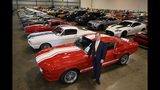 FILE - In this Sept. 16, 2019 photo, McGregor Scott, U.S. Attorney for the Eastern District of California, stands next to a 1967 Ford Shelby GT 500, that was seized along with other cars by the federal government that are now housed in a warehouse in Woodland, Calif. Two employees of a defunct San Francisco Bay Area solar energy company pleaded guilty Tuesday, Oct. 22, 2019, to participating in what federal prosecutors say was a massive $2.5 billion fraud scheme that defrauded investors of $1 billion. It's the largest single-owner car collection ever auctioned by the U.S. Marshals Service, with vehicles to be auctioned off on Wednesday. (Randy Pench/The Sacramento Bee via AP)