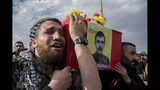 People attend funerls of Syrian Democratic Forces fighters killed recently fighting Turkish forces in the town of Hasakeh, north Syria, Monday, Oct. 21, 2019. (AP Photo/Baderkhan Ahmad)