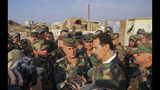 """In this photo released on the official Facebook page of the Syrian Presidency, Syrian President Bashar Assad, center right, speaks with Syrian troops during his visit to the strategic town of Habeet, in the northwestern province of Idlib, Syria, Tuesday, Oct. 22, 2019. On Tuesday, Assad called the Turkish President Recep Tayyip Erdogan a """"thief"""" during his first visit to territory captured from Turkey-backed rebels in the northwestern province of Idlib. (Facebook page of the Syrian Presidency via AP)"""