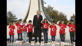 Turkish President Recep Tayyip Erdogan poses for photos with primary school students from a village of Black Sea city of Samsun, who give a military style salute outside the presidential palace, in Ankara Monday, Oct. 21, 2019. Erdogan has responded angrily to widespread criticism in the West of Turkey's incursion in northeast Syria.(Presidential Press Service via AP, Pool )